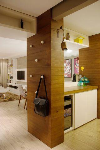Detalhe da divisão entre sala e cozinha: puxadores de madeira foram dispostos pela parede e servem de mancebo.
