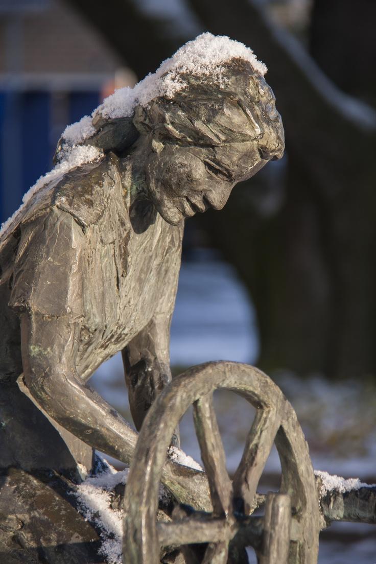 """Bronzen beeld van een vrouw aan een spinnewiel. Kunstenaar is Antoinette Ruiter (1946), beeldhouwster te Oldenzaal. geschonken door vereniging """"openbaar belang"""" 19 april 1990"""