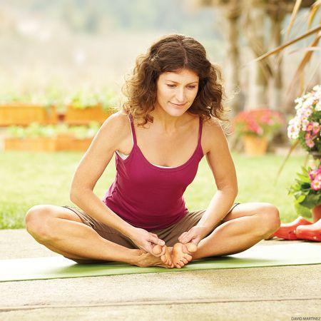 woman doing yoga outside in garden cobbler's baddha konasana bound angle butterfly pose