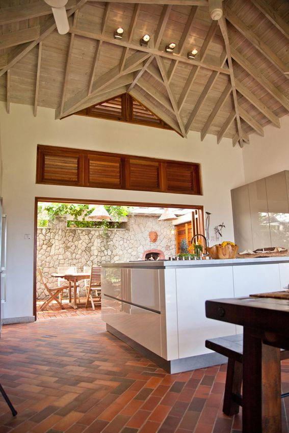A stunning villa in the caribbean by Nomade Architettura http://www.nomadearchitettura.com/#all  timber roof in a wonderful custom made white and grey kitchen, local bricks on the floor