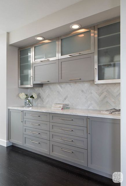 Soft patterning is added in the kitchen's buffet area with a Herringbone Calacatta tile backsplash. The gray painted cabinets have a more modern feel with frosted glass fronts and brushed stainless hardware.