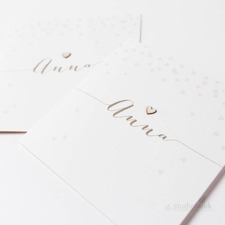 Geboortekaartje voor meisje met haar naam in het bling goud en hartjes roze. Als kers op de taart is er een houten  mini-hartje boven haar naam bevestigd. Hoé bijzonder! Meer informatie? Stuur een mailtje naar info@studiokuuk.nl