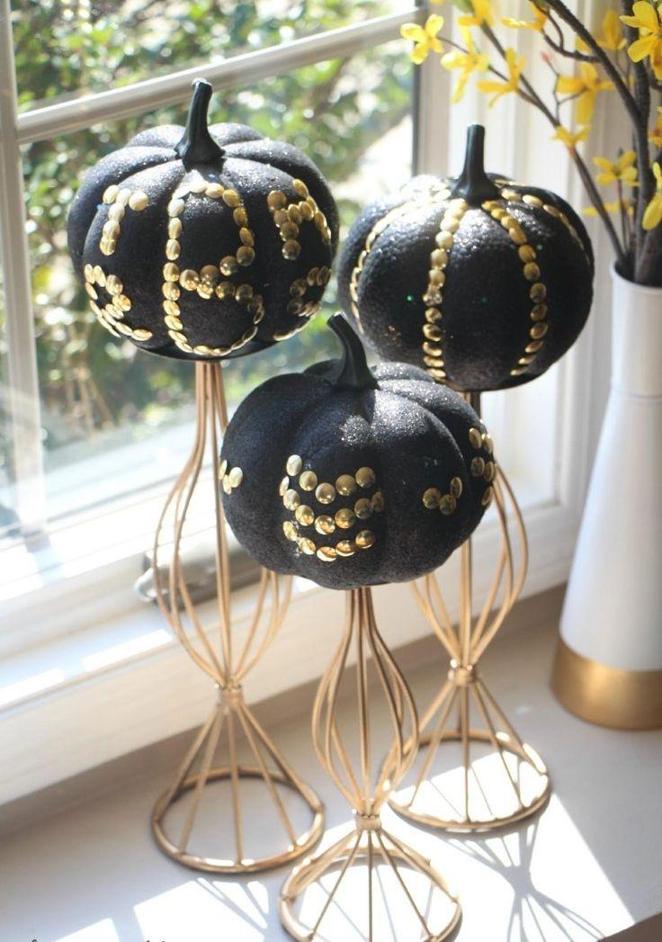 déco citrouille - des mini-citrouilles peintes noires et décorées de punaises, sur des supports en métal
