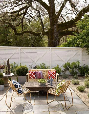 white washed fence: A Living Room Outdoors Invite guests over, or enjoy this casual outdoor space by yourself with a glass of iced tea. It's just like bringing your living room outdoors. Vintage metal glider and chairs from Zonal. Pillows from Pottery Barn.