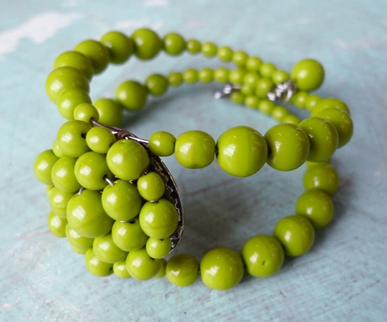 Chartreuse bracelet with large focal piece ... I'm thinking salvaged vintage brooch or earring and necklace beads.