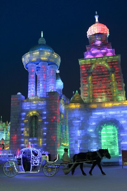 Horse drawn carriage moving by a Russian ice palace at the Harbin ice festival in Heilongjiang, China.
