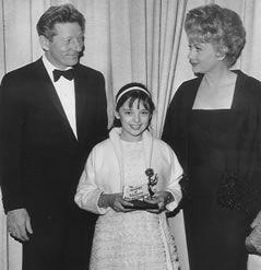 """Herkomst van deze foto heb ik (nog) niet kunnen achterhalen. Het meisje op deze foto is Angela Cartwright; een soort van """"kindsterretje""""; begonnen als kindermodel en ging later ook acteren. De relatie tussen haar en Danny en Lucy Ball heb ik niet kunnen vinden; de foto is van begin zestiger jaren, omdat Angela in 1955 geboren werd. Blijkbaar heeft Angela een soort van prijs gewonnen? Het zou te maken kunnen hebben met de TV-serie """"Make room for Daddy"""" uit de zestiger jaren."""