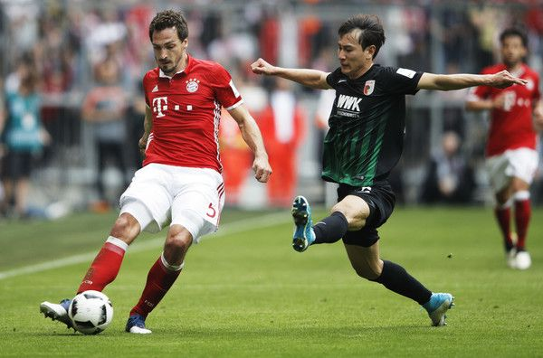 Ji Dong Won Photos - Mats Hummels of Bayern Munich is challenged by Ji Dong-Won of Augsburg during the Bundesliga match between Bayern Muenchen and FC Augsburg at Allianz Arena on April 1, 2017 in Munich, Germany. - Bayern Muenchen v FC Augsburg - Bundesliga