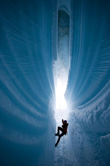 A climber rappels 300 feet down into the Greenland ice sheet.