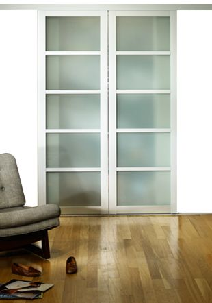 Frontal view of a Sliding door with metal frame and semi-opaque glass. A classic room interior surrounds it.