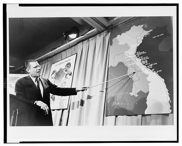 [Sec. of Defense Robert McNamara pointing to a map of Vietnam at a press conference]