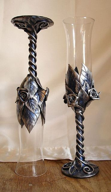 This is a set of tall clear flutes with roses, leaves and vines sculpted from black clay, then colored with silver and shimmery blue mica powder.