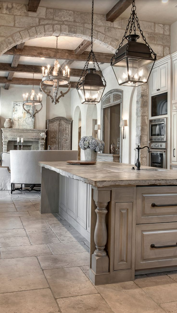 French country kitchens - The Unfinished Edge Of This Counter Distressed Grey Cabinetry Pendant Lantern Lighting