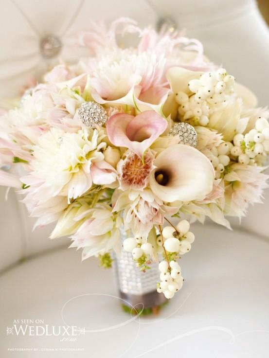 The bridal bouquet will be made of blush mini calla lilies, blushing bride protea, snowberries, white dahlias, blush nerines, and brooch accents wrapped in jewel wrapping.