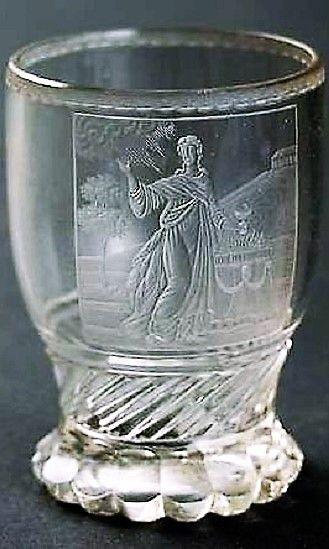 Sklenice z čirého skla se segmentovanou patkou, zdobená jemnou řezbou s motivem alegorie Víry jako hlavní z teologických ctností. Prvotřídní řezba pochází pravděpodobně z dílny Antona Simma, případně z jeho nejbližšího okruhu. V. 12 cm.