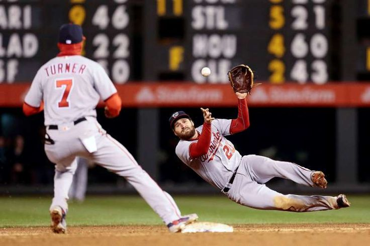 DOUBLE PLAY:    Daniel Murphy of the Nationals makes a throw to Trea Turner who turns a double play against the Rockies on April 25 in Denver. The Nationals Won 16-5.