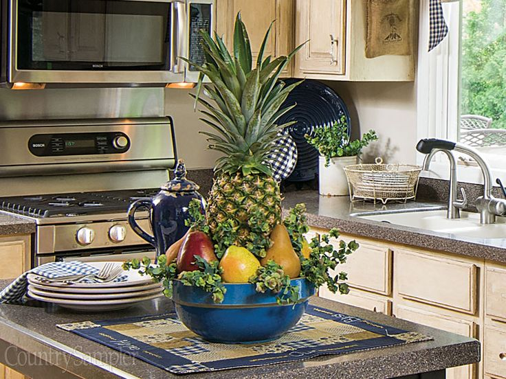 Build a pretty centerpiece by arranging smaller fruits around a pineapple and tucking in sprigs of oregano for texture.