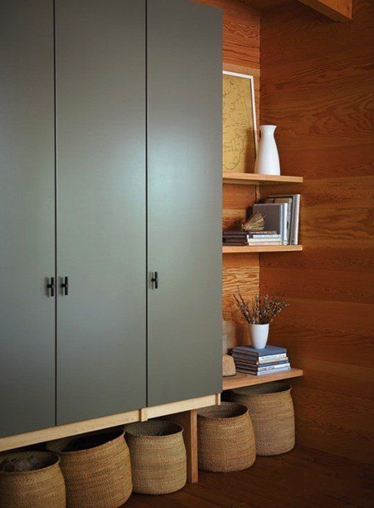 Lovely rendition of Ikea Pax wardrobes. Wood-wrapped walls, baskets beneath, earthy paint color for doors...give a natural feel to a big-box product.