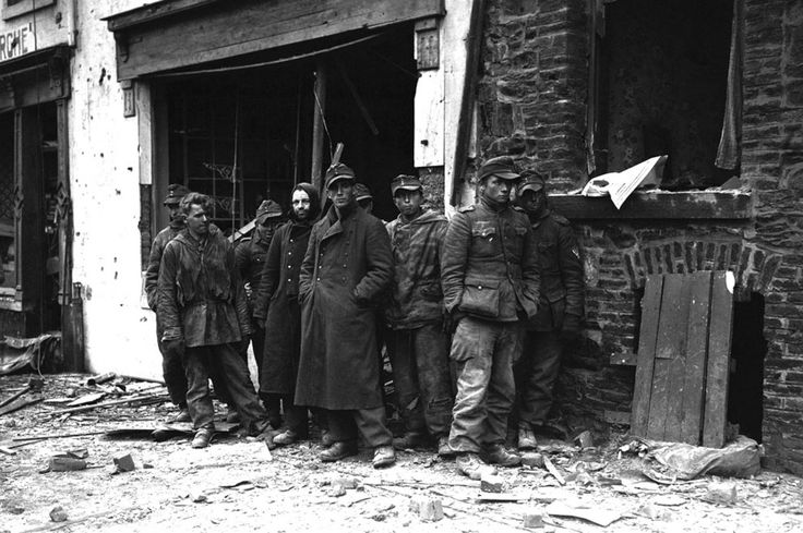 """Caption: """"German POWs stand in the debris strewn street after the Siege of Bastogne, where they were captured by the U.S. 4th Armored Division which helped break the German encirclement and occupation of the town. Bastogne, Province of Luxembourg, Belgium. January 1945. """""""