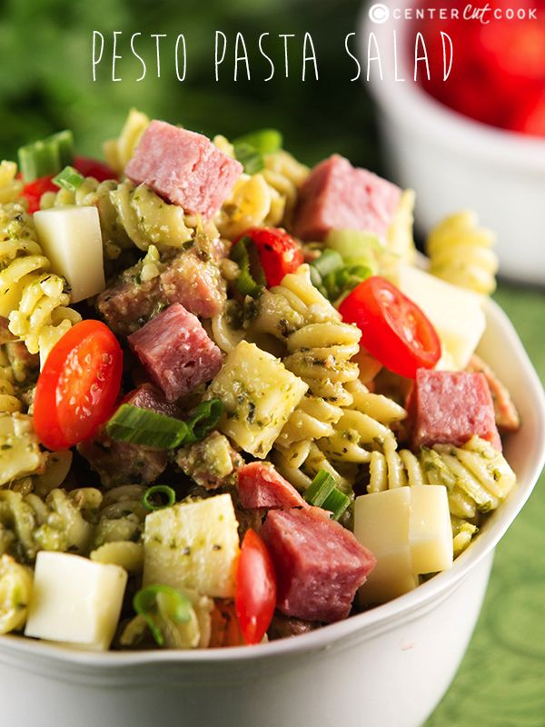 An easy Pesto Pasta Salad recipe tossed with creamy basil pesto dressing, grape tomatoes, chunks of salami, and cubed mozzarella cheese.