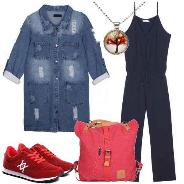 In questo outfit la jumpsuit blu, con bretelline e coulisse in vita, è indossata in versione casual con una giacca lunga di jeans effetto consumato, sneakers vintage e borsa tote in ecopelle rossa, collana con ciondolo colorato.