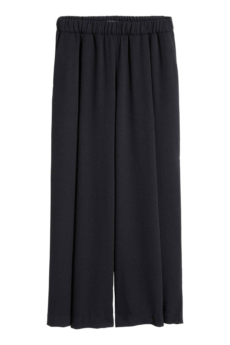 Wijde broek: Een wijde broek van crêpekwaliteit met breed elastiek in de taille, bandplooien en steekzakken.