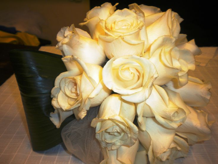 Ramo redondo con rosas crema, hoja y tul.