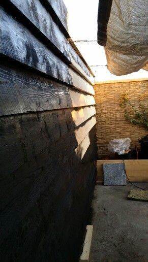 De schuur is gepotdekseld met stijgerhout en zwart geverfd