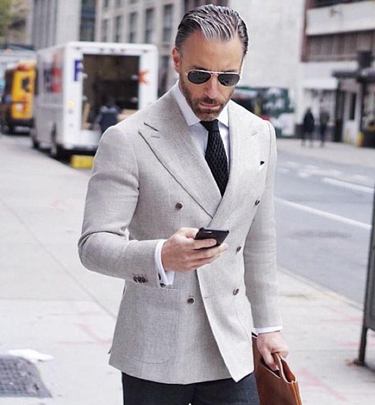 Acheter la tenue sur Lookastic: https://lookastic.fr/mode-homme/tenues/blazer-croise-chemise-de-ville-pantalon-de-costume/21297 — Chemise de ville blanche — Cravate en tricot noir — Blazer croisé gris — Pantalon de costume noir — Serviette en cuir brune claire