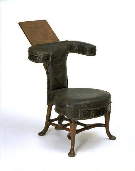 """""""The oddest chair I'd ever seen required a longer pause. Its high, deeply curved back had a leather-covered bookstand mounted on it, and the seat was shaped rather like a saddle. The only way to occupy the chair would be to sit astride it, as Gallowglass did whenever he turned a chair at the dining-room table."""" [Reading chair - Great Britain,1720-30]"""