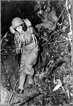 """""""Two United States Army nurses carry heavy combat packs on a eight-mile hike through the jungle as part of their training before taking up front-line war assignments. Before reporting for duty the American nurses learn how to combat jungle hazards and how to care both for themselves and their patients under all conditions."""""""