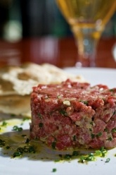 Steak Tartar - Lean ground beef served raw with capers, cornichons, onions, egg yolk and la goulues own spice blend. From La Goulue in Miami Beach, FL.