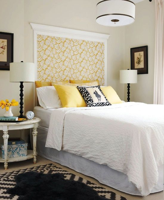 """Master bedroom in black, white and yellow with a wall """"mounted"""" headboard made out of floral wallpaper and left over crown moldings."""