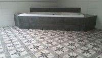 Een imitatie cementtegel welke uitermate geschikt is als alternatief. Hier toegepast in een badkamer. Voordeel van dit alternatief t.o.v. de originele cementtegels is dat het  geen onderhoud nodig heeft en gewoon bestand is tegen de alledaagse schoonmaakproducten.