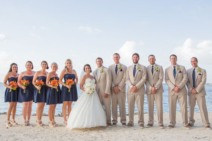 Groomsmen in khaki suits and blue ties  stand by the beachfront sandy edge at Key Largo Lighthouse Beach Wedding Venue in the Florida Keys