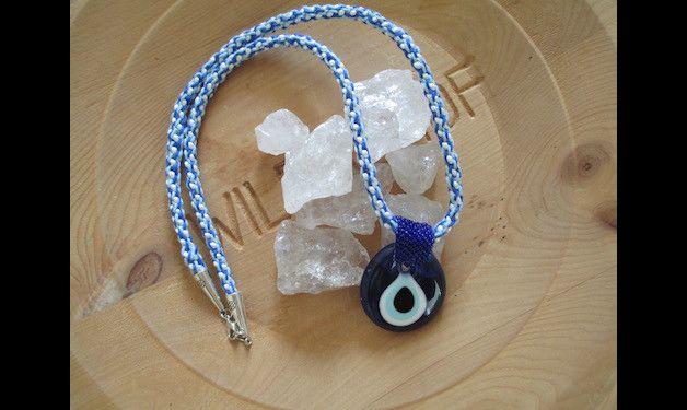 Kumihimo ketting gemaakt van wit satijnkoord en twee kleuren blauw katoen. Aan de ketting hangt een zogenaamd Turks boze oog amulet van glas. Het is bevestigd met donkerblauwe kraaltjes. De ketting...