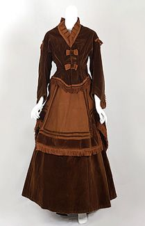 Three-piece promenade ensemble, c.1867. The outfit consists of a sepia brown velvet bodice and underskirt together with contrasting copper brown faille overskirt. The pulled-back skirt construction anticipates bustle styles of the 1870s.