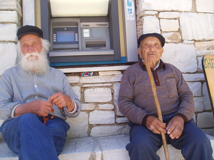 NAXOS  Traditional villagers juxtaposed to the ATM machine.