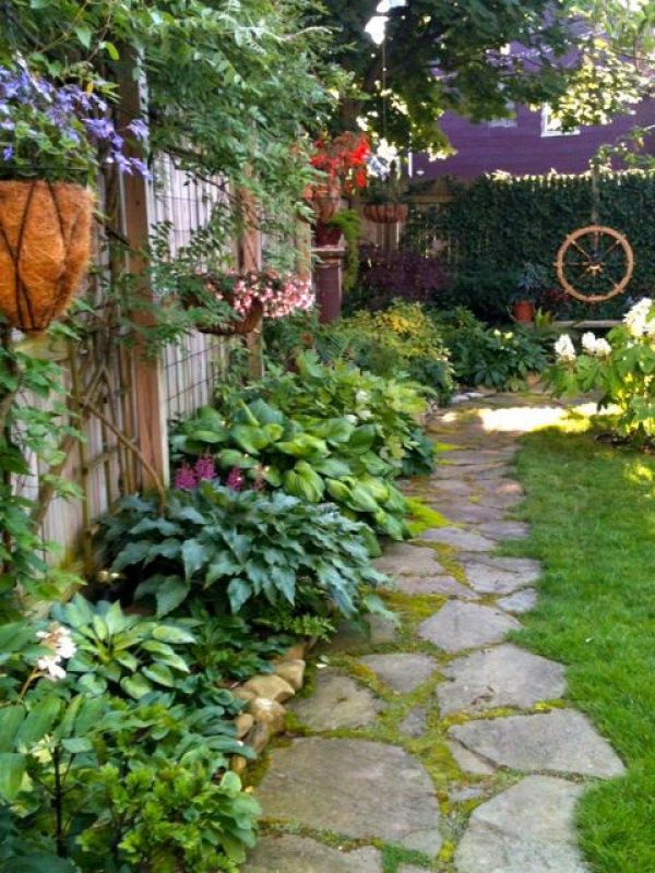 shady side of house plantings... hosta, astillbe, ferns, & more.... stone instead of grass- starting at driveway leading to back