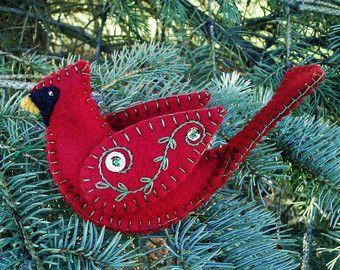 Este único ornamento cardinal femenino es una combinación perfecta para el adorno cardinal masculino en esta tienda. Ella es tridimensional y puede visualizarse desde cualquier ángulo. Tamaño aproximado es 3 x 5 1/2 largo x 1 1/2 ancho alto. Hecho en el estilo de arte popular, este ornamento de pájaro está hecha de tan color 100% fieltro de las lanas. Las alas son bordadas en color verde pálido y adornadas con cuentas y lentejuelas rojos y verdes. La cola es bordada en rojo y adornada con…