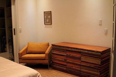 Quarto aconchegante com cômoda de madeira colorida e poltrona Fernando Jaeger. Quadros decorativos.