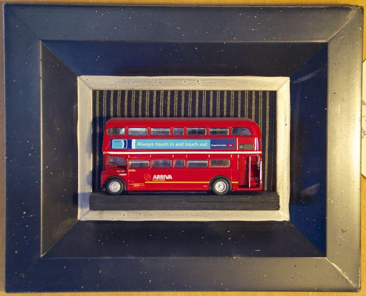 Modellbuss av en RML (Routemaster Long) kjøpt på London Transport Museum og rammet inn i en ferdigramme fra Gave&Interiør på Hamar. En skrue er boret inn i modellen og holder den på plass.