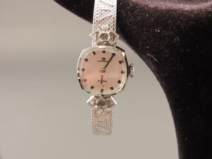 """Elegante orologio da signora (carica manuale, funzionante) degli anni '70 in oro bianco 18 carati e 2 punti di diamanti naturali. Quadrante color argento satinato, con piccoli """"saltarelli"""" e lancette in metallo argentato, firmato Lorenz, Edox. Il cinturino (con due misure), imitante il tessuto, con particolare motivo geometrico, è originale Lorenz ed è anch'esso in oro bianco 18 carati. In vendita su www.mirabilia.gallery per  1.770,00 € (Iva inclusa)."""
