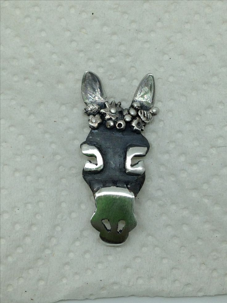 Hand made donkey brooch by Helen Green, made using silver sheet, metal clay flowers and liver of sulphur to oxidise areas.