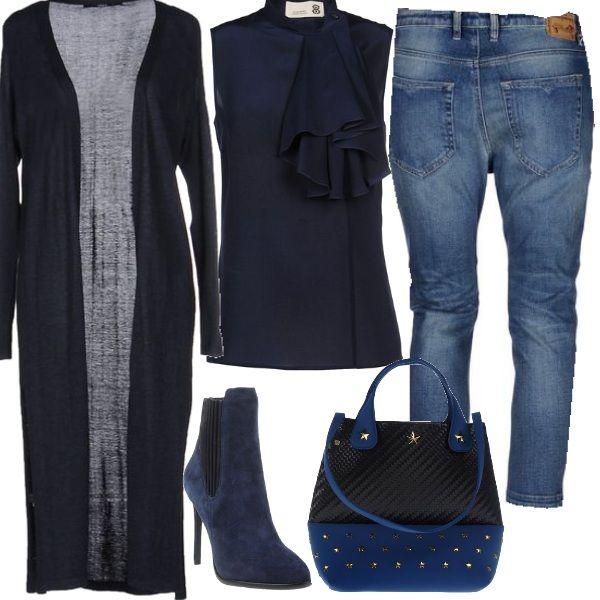 Casual ma elegante con i jeans 7/8 indossati con una camicia senza maniche in crepe di seta, impreziosita da una rouche nel colletto. Per completare la composizione un cardigan blu, lungo come un cappotto. stiletti con tacco alto e una borsa a mano bicolore con decorazioni in metallo.