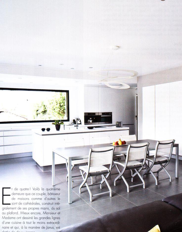 Une cuisine blanche parfaitement intégrée dans les murs et autour de la grande fenêtre panoramique. Ilot de préparation bien pratique. Cuisine et Bains Magazine 137