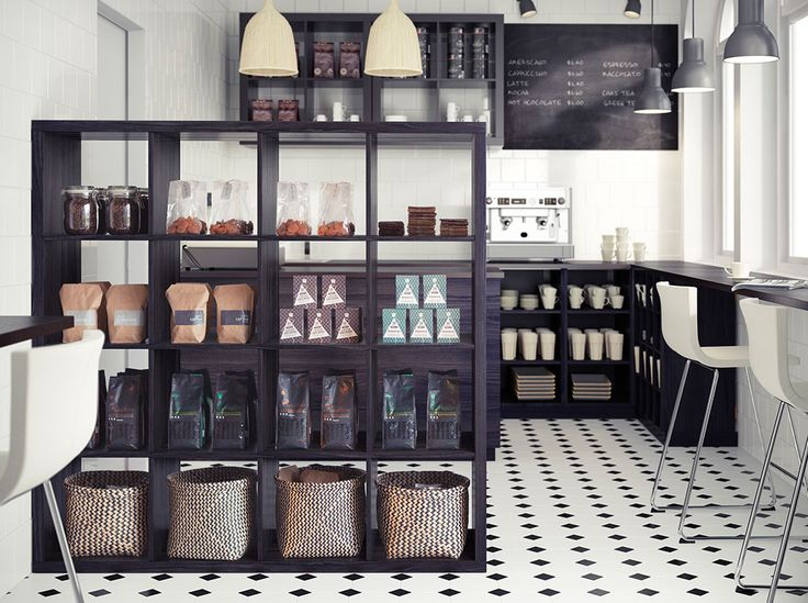 A coffee shop with black-brown shelving units, black base cabinets and white/chrome-plated bar stools with backrest