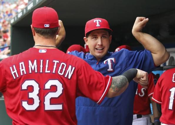 Texas Rangers starting pitcher Derek Holland (45) compares muscles with Texas Rangers left fielder Josh Hamilton (32) in the dugout before the Arizona Diamondbacks vs. the Texas Rangers major league baseball game at Globe Life Park in Arlington on Tuesday, July 7, 2015. (Louis DeLuca/The Dallas Morning News)