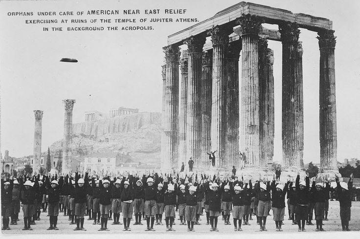 Ορφανά κάτω από την προστασία της Επιτροπής Αμερικανικής Μέριμνας για τη Μέση & Εγγύς Ανατολή, στον περίγυρο του Ναού του Διός στην Αθήνα με φόντο την Ακρόπολη. Η φωτο ανήκει στον Ερυθρό Σταυρό και βρίσκεται στο Library of Congress.