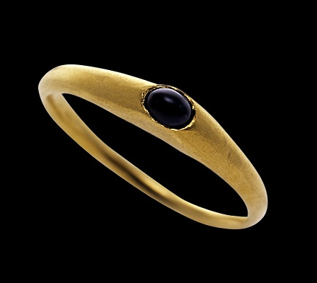 Gold, the stirrup shaped ring rising to an apex set with a cabochon sapphire. English, c. 1200